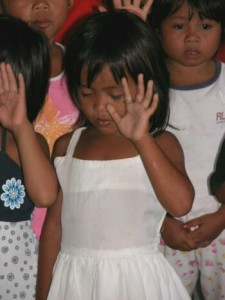 "Young girl surrendering her life to Christ  during the ""Mission Smile"" project in a   remote village near Cagayan de Oro, Philippines."
