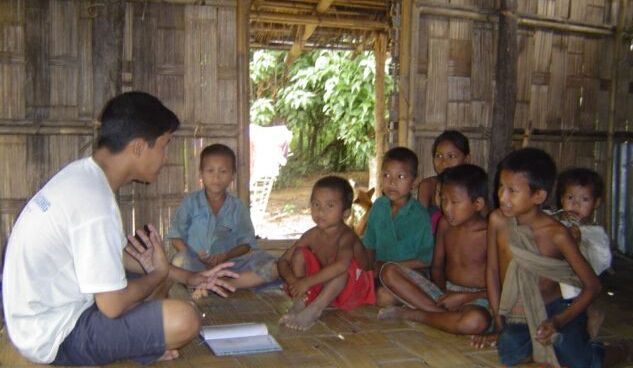 Teacher in Asia teaches the Word of God to the children in a remote village.