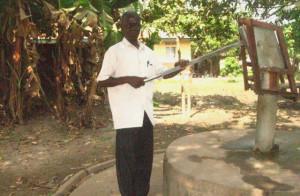 Pastor Emmanuel testing the hand pump