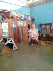 Sister Anita standing in her flooded bedroom